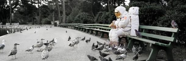 Astronaut feeding pigeons on a park bench