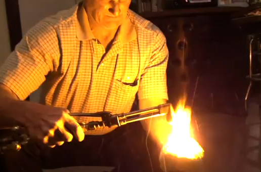 A man taking a torch to his hand