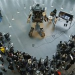 "Journalists surround a giant ""Kuratas"" robot at an exhibition in Tokyo"